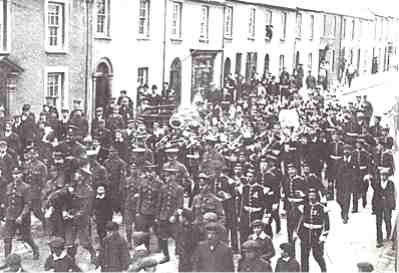The champions! The Rugby team of the 2nd battalion, the Welsh Regiment won the  the 1911-12 season cup. Here, complete with band, they carry the trophy shoulder high  down Laws Street.